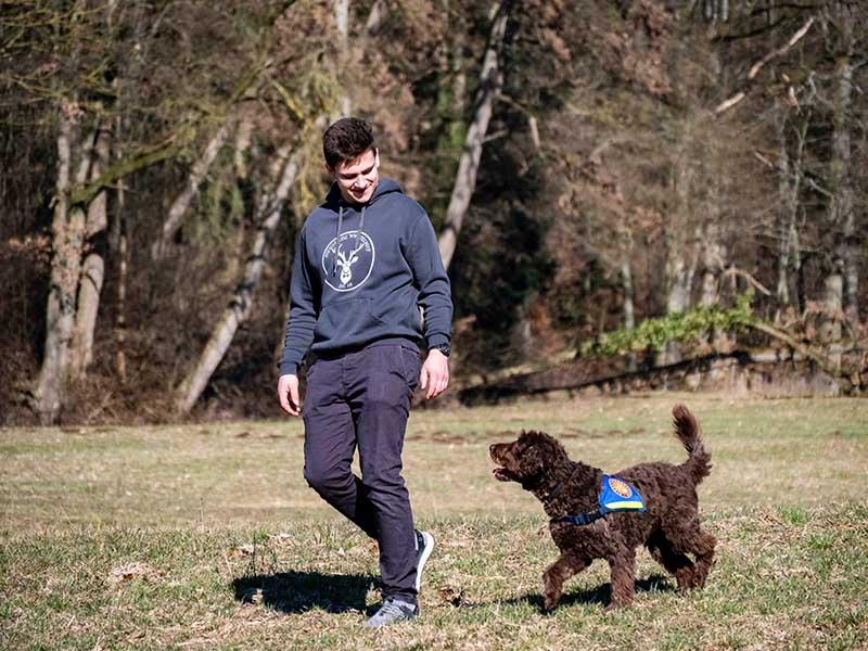hundeschule-susanne-kohler-bühlerzell - ein junger mann und sein diabetikerwarnhund laufen über eine waldwiese