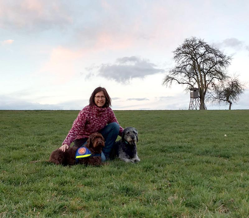 hundeschule-susanne-kohler-bühlerzell - man sieht susanne kohler mit ihren beiden hunden auf einer wiese sitzen vor beeindruckendem abendhimmel