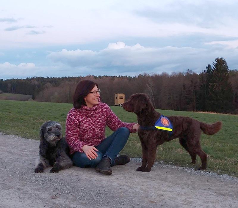 hundeschule-susanne-kohler-bühlerzell - susanne kohler sitzt lachend mit ihren beiden hunden auf einem feldweg